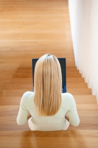 Woman using laptop on stairs